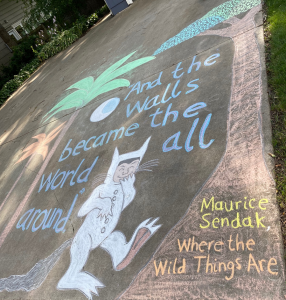 "Chalk drawing of trees and the character Max from Where the Wild Things Are. Caption: ""And the walls became the world all around. - Maurice Sendak, Where the Wild Things Are"""