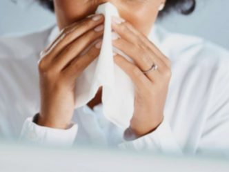 Woman sneezing into tissue.