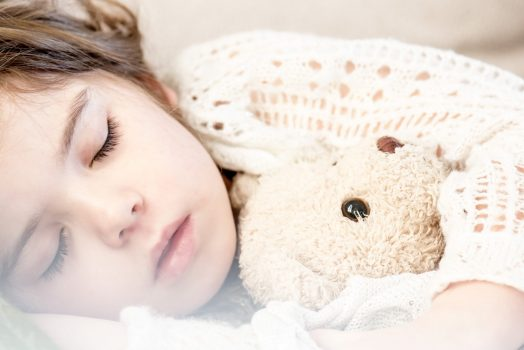 Girl napping with a bear.