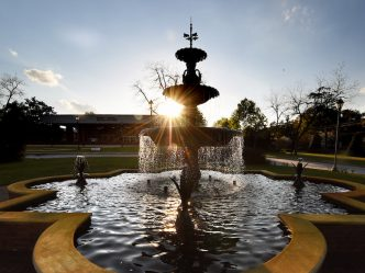 The fountain at sunrise with Maxwell Theatre in the distance.