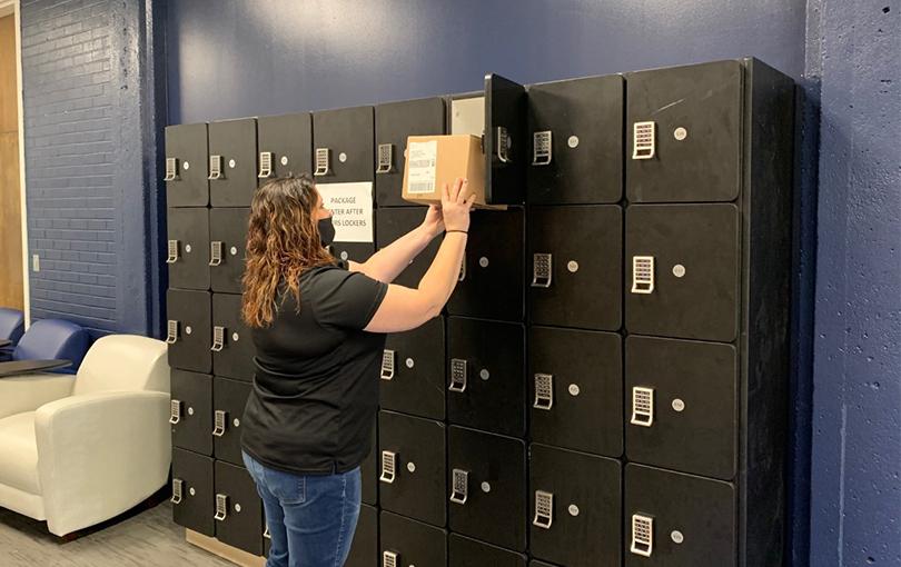 woman puts box in locker