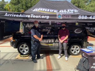 "wearing masks, a male police officer and man stand under a tent, in front of a car with ""Arrive Alive Tour"" branding on it"