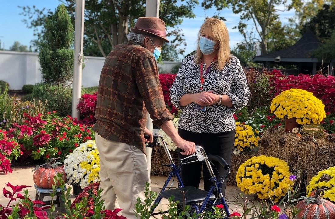 woman standing and male veteran using walker