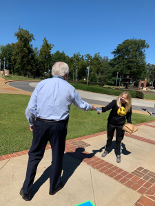 President Keel hands a T-shirt to a female student on the Summerville Campus