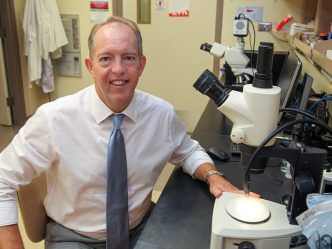 Man at microscope smiling