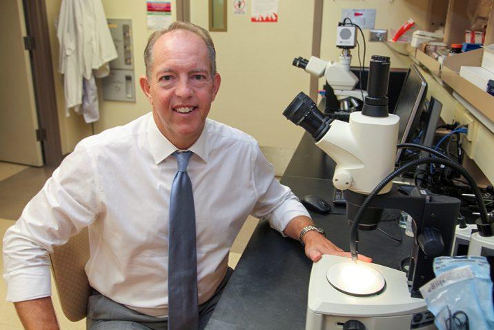 Man at microscope smiling
