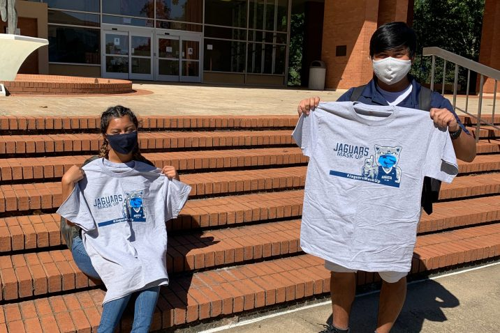 two students hold up grey Jaguars Mask Up T-shirt