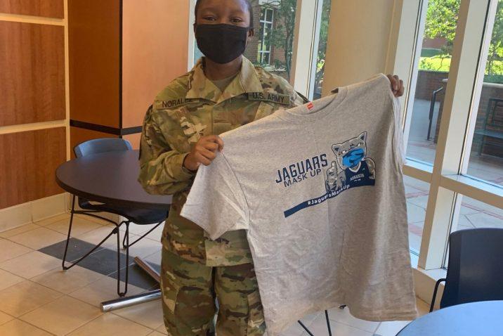 masked student holds up grey Jaguars Mask Up T-shirt
