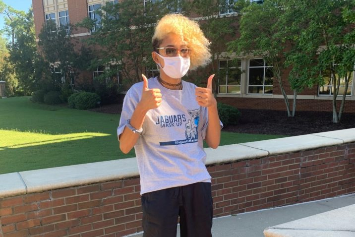 student giving a thumbs-up and wearing grey Jaguars Mask Up T-shirt