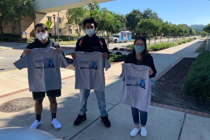 3 masked students hold up grey Jaguars Mask Up T-shirts