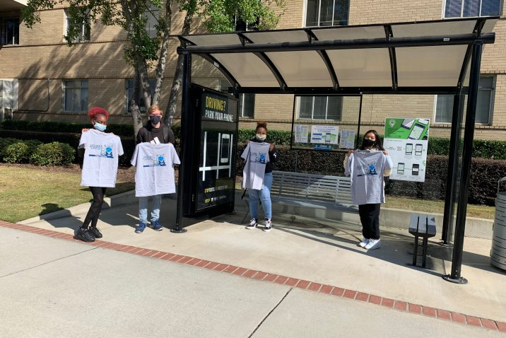 four students at bus stop pose with grey Jaguars Mask Up T-shirts