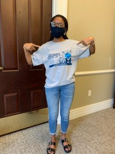 "Woman in glasses and a mask poses wearing grey ""Jaguars Mask Up"" t-shirt"