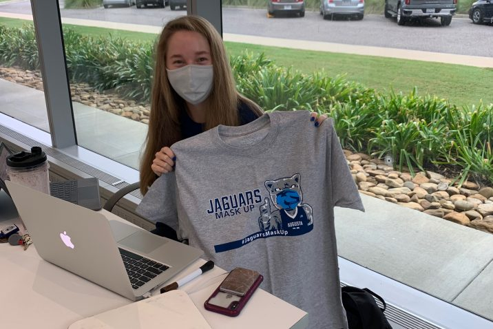 student sitting at a table on her computer holds up grey Jaguars Mask Up T-shirt