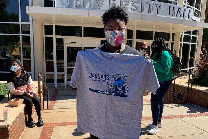 student holds up grey Jaguars Mask Up T-shirt