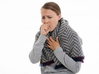 Woman coughing into her hand.