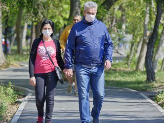 Older man and woman holding hands while walking and wearing face masks.