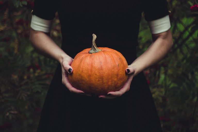 A woman holding a pumpkin.
