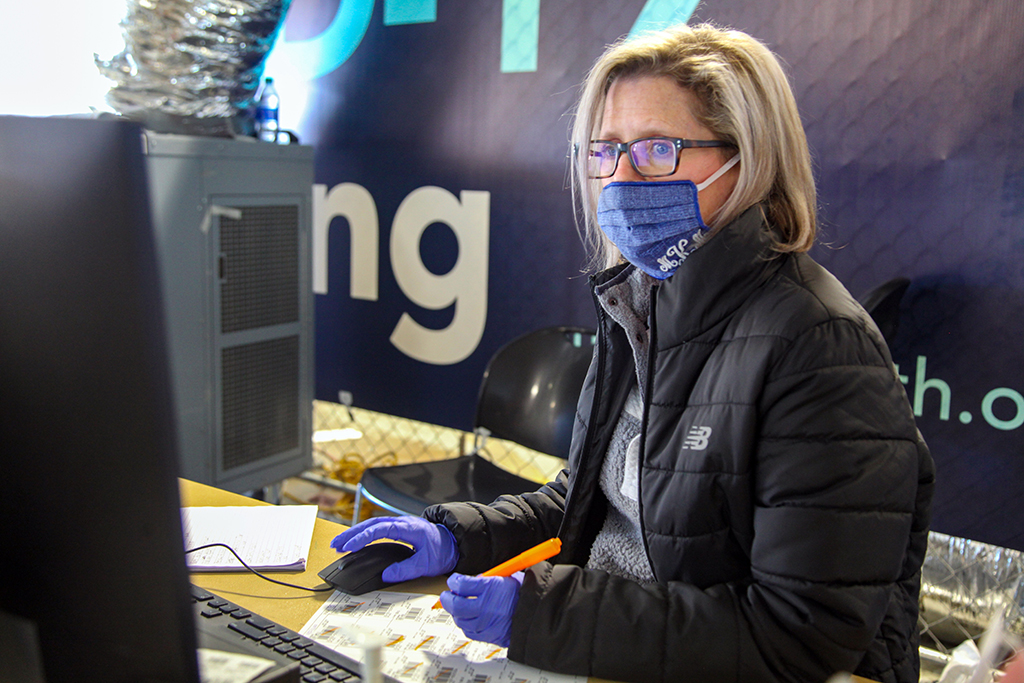 Woman in jacket and mask at computer