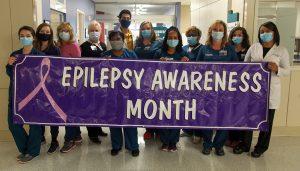 Members of Neurodiagnostics holding a banner
