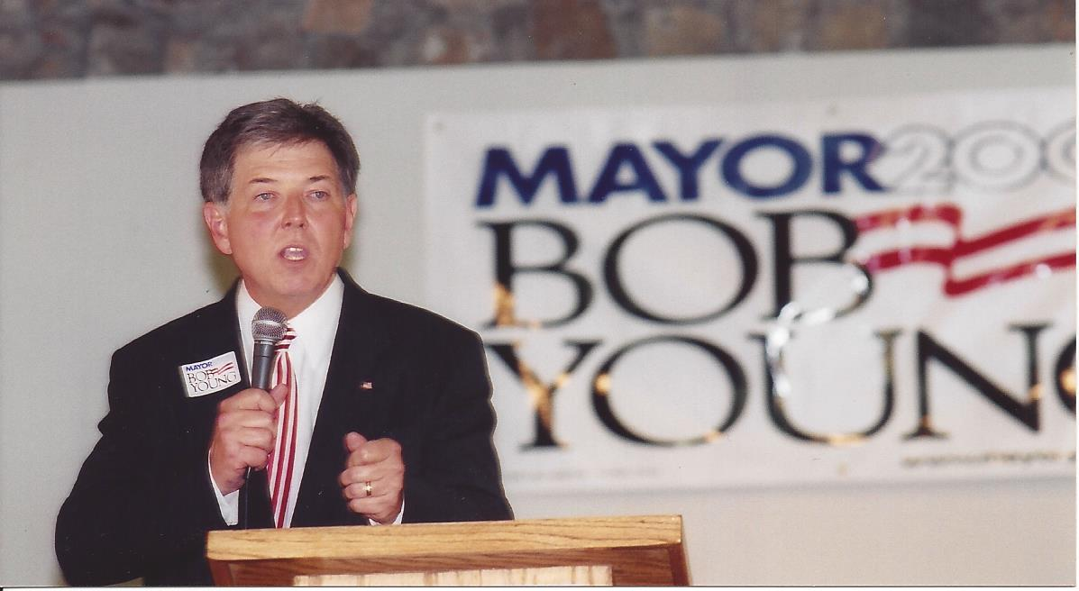 politician in front of sign