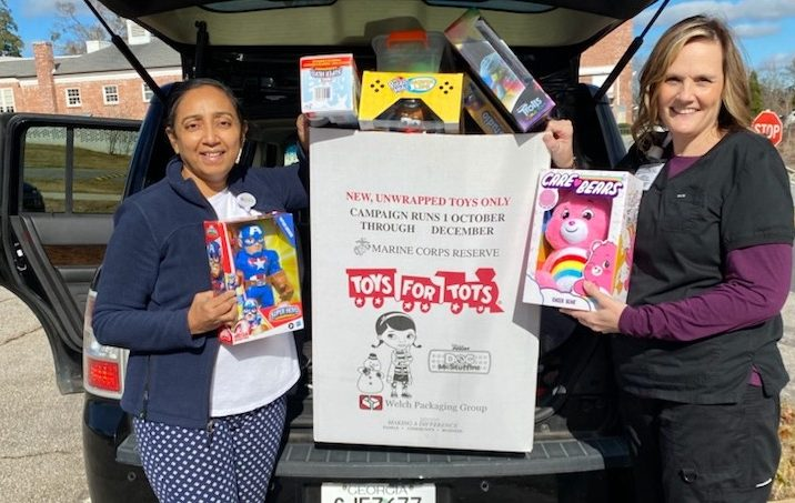 women next to car with toys in back