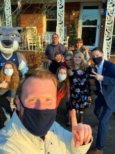 9 people pose for a selfie with the Augustus mascot