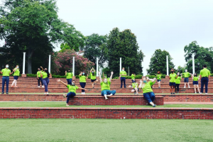 group of students in lime green polos pose in the Augusta University amphitheatre