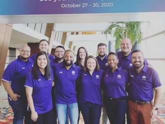11 men and women in purple collared shirts smile for a photo
