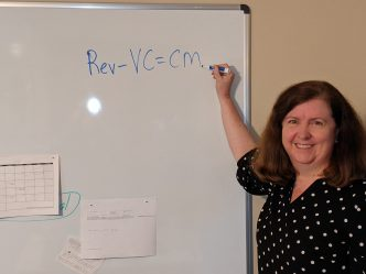 A woman writing on a dry erase board.