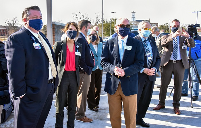 masked university leaders gather to watch