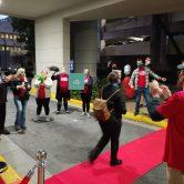 woman walks on red carpet as people applaud