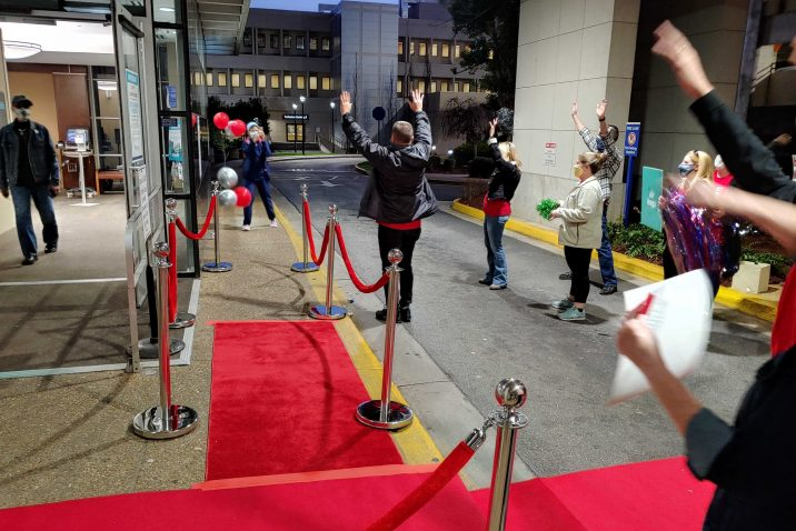 people cheer as woman approaches red carpet