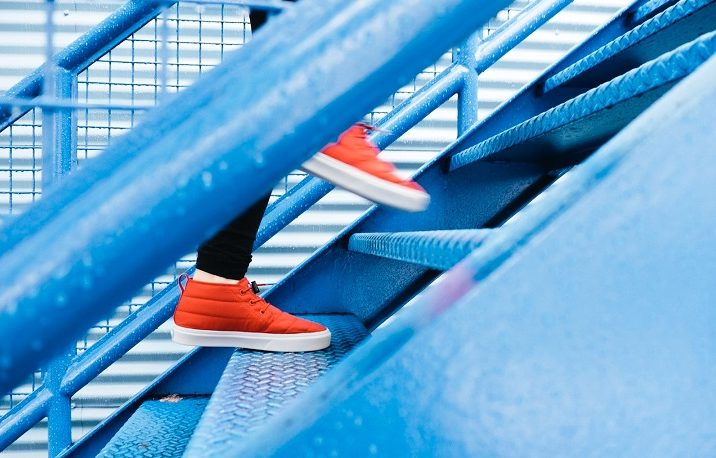 red sneakers going up blue stairway