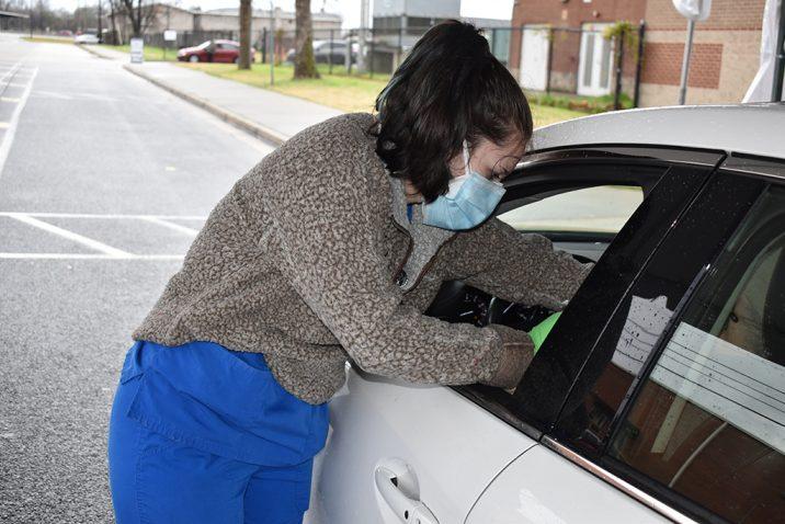 nurse helping patient in car