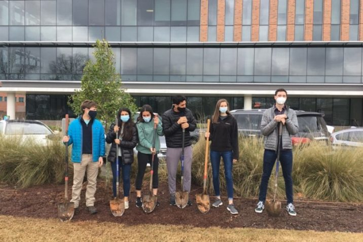 six young adults stand with shovels outside