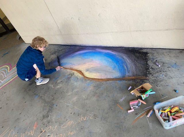 boy making chalk drawing