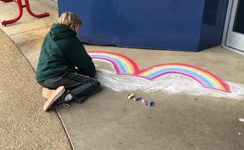 boy draws rainbows with chalk