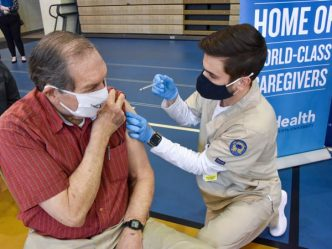A man getting a shot from a nurse.