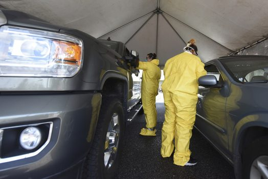 Two workers in PPE testing patients inside cars