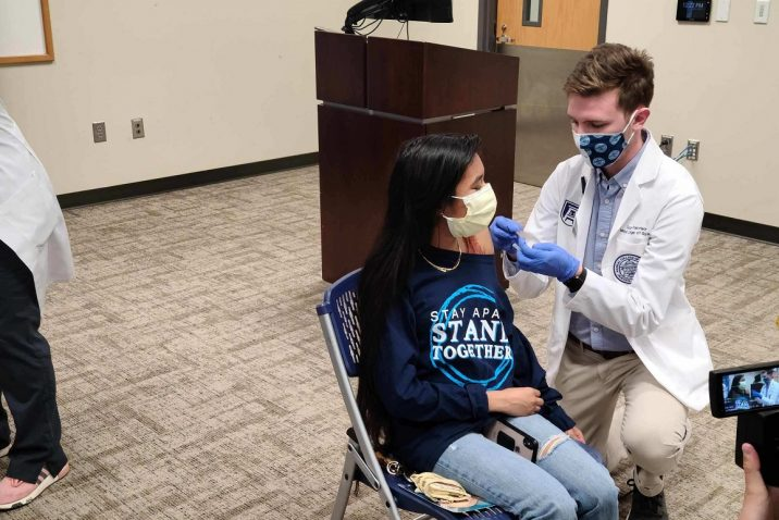 male doctor vaccinates female student