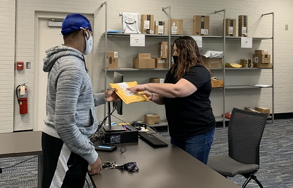 student accepts envelope from mail person