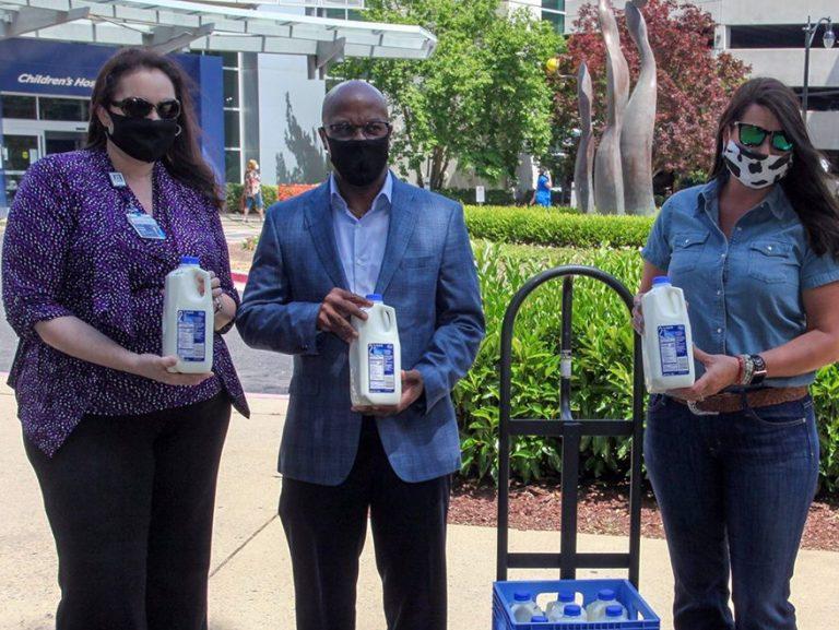 three people holding half gallons of milk