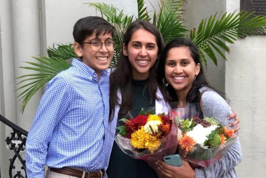 A brother and his two sisters, one sister holding flowers, smile for a photo
