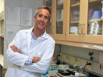 Dr. Eric Belin de Chantemele, in a white lab coat, leans next to a counter in his lab