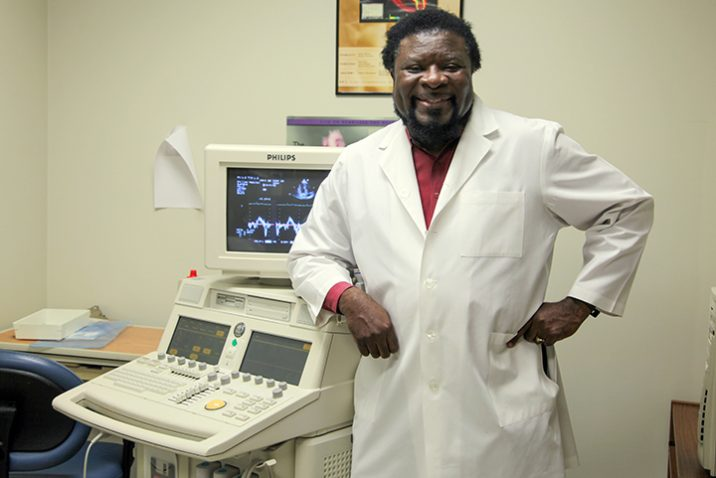 Dr. Gaston Kapuku, in white lab coat, stands in front of lab equipment