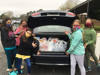 Students with a trunk full of groceries in bags