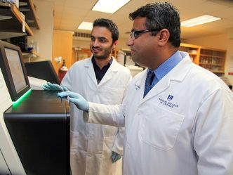 Dr. Ravindra Kolhe stands in the forefront of a lab with his research associate looking on