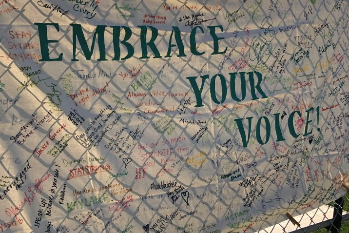 large sign with signatures says 'Embrace your voice'
