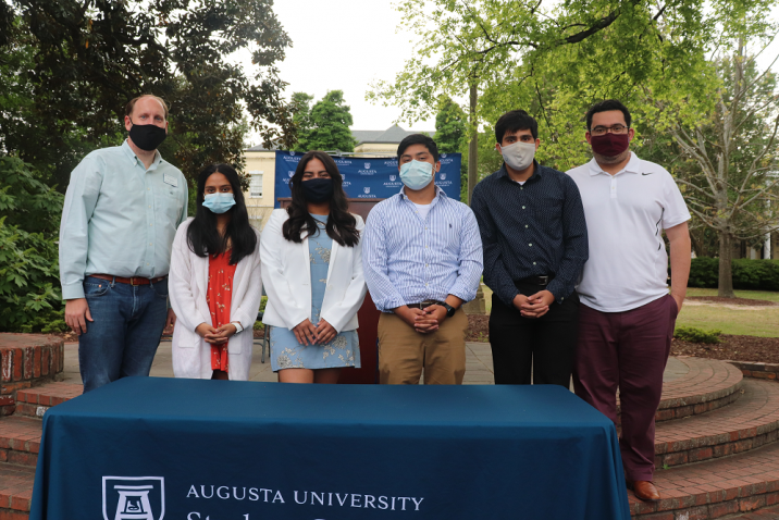 "Six people, all wearing masked, stand behind a table with a tablecloth that reads ""Student Government Association"""