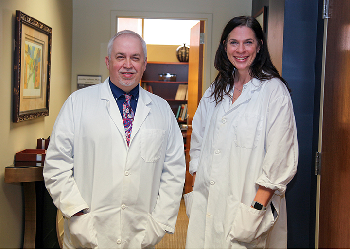 Drs. David Step (on left) and Jennifer Sullivan stand in hallway in white lab coats